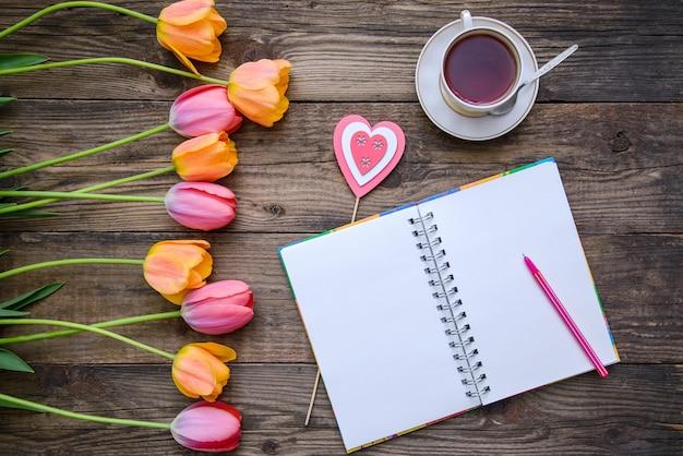 Tulipanes, cuaderno, taza de té y corazón sobre fondo de madera