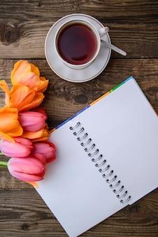Tulipanes, cuaderno, taza de té sobre fondo de madera