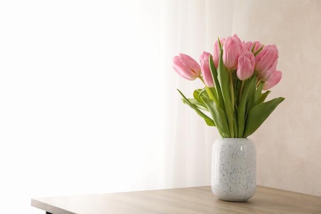 Tulipanes en florero sobre fondo de madera, espacio para texto