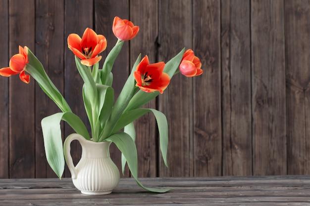 Tulipanes en florero sobre fondo de madera oscura