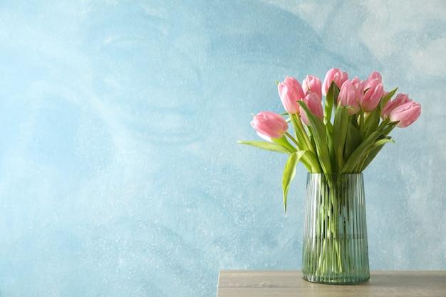 Tulipanes en florero sobre mesa de madera, espacio para texto