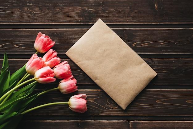 Tulipanes de flores de color rosa con un sobre postal de papel sobre una mesa rústica de madera