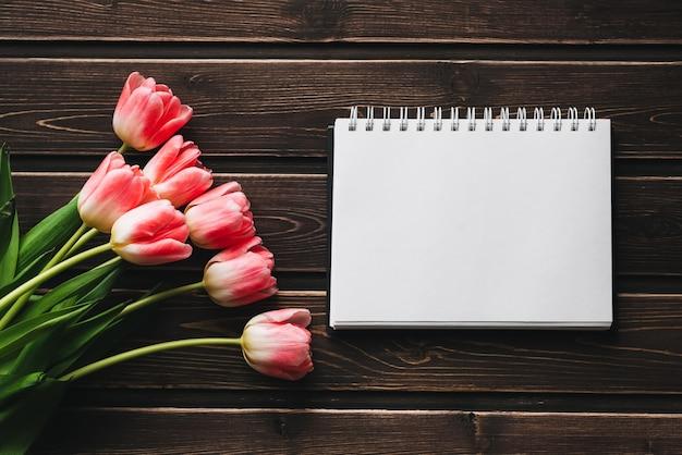 Tulipanes de flores rosadas con bloc de notas en blanco sobre mesa de madera para tarjeta de felicitación