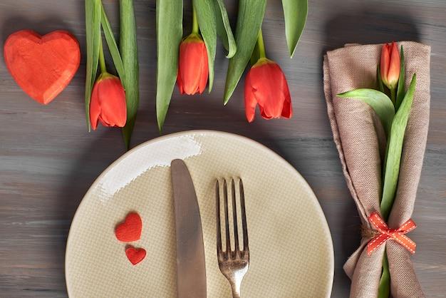 Tulipanes frescos y decoraciones de corazón en gris