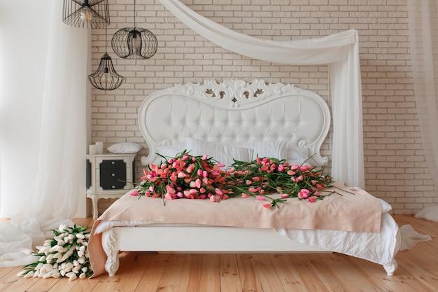 Tulipanes hermosos rojos y blancos en cama clásica grande en fondo de la pared de ladrillo