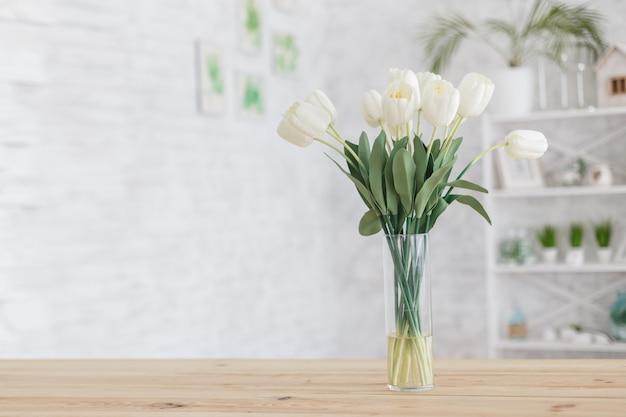 Tulipanes en un jarrón sobre una mesa de madera. interior escandinavo.