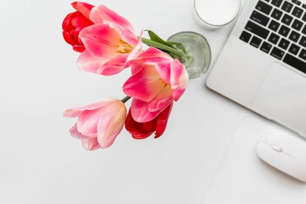 Tulipanes y laptop en mesa blanca