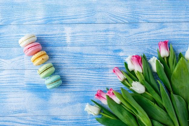 Tulipanes con macarrones en superficie de madera azul