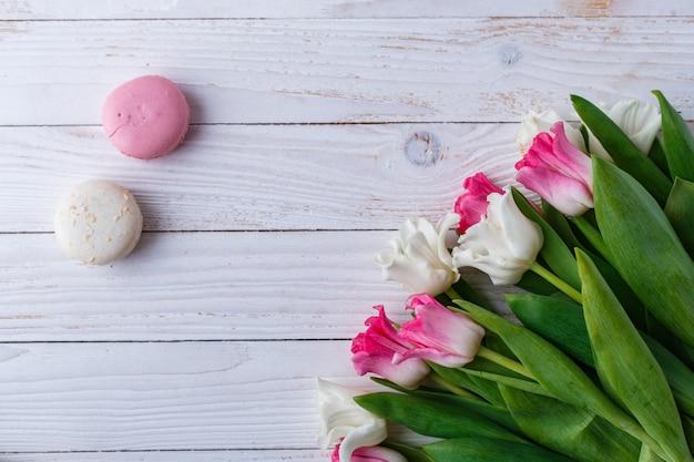Tulipanes con macarrones en la superficie de madera blanca