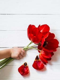 Tulipanes en manos de un niño