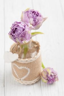 Tulipanes morados en botella con corazones