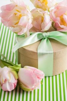 Tulipanes morados rosados y caja de regalo con cinta verde