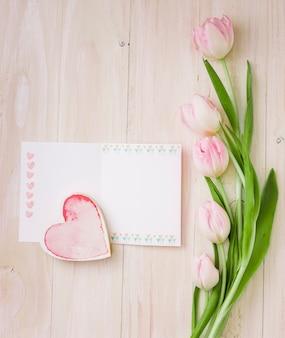 Tulipanes con papel en blanco y corazón