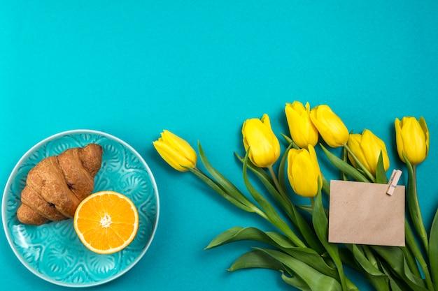Tulipanes con papel en blanco y croissant.