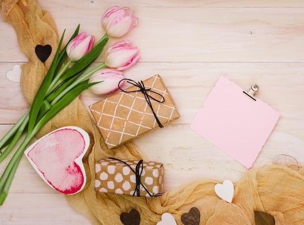 Tulipanes con pequeñas cajas de regalo y papel.