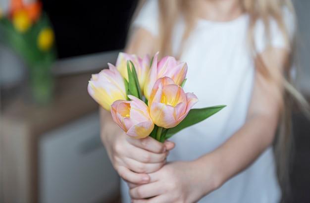 Tulipanes de primavera en manos de una niña