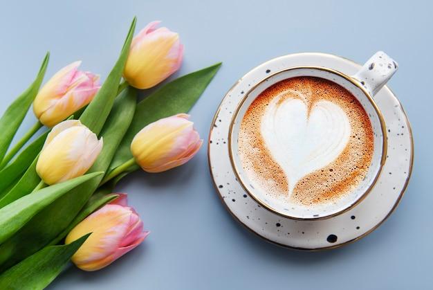 Tulipanes de primavera y taza de café sobre un fondo azul.
