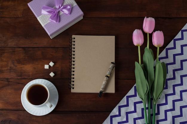 Tulipanes, regalo, taza con café, cuaderno sobre una superficie de madera oscura. vista superior plana