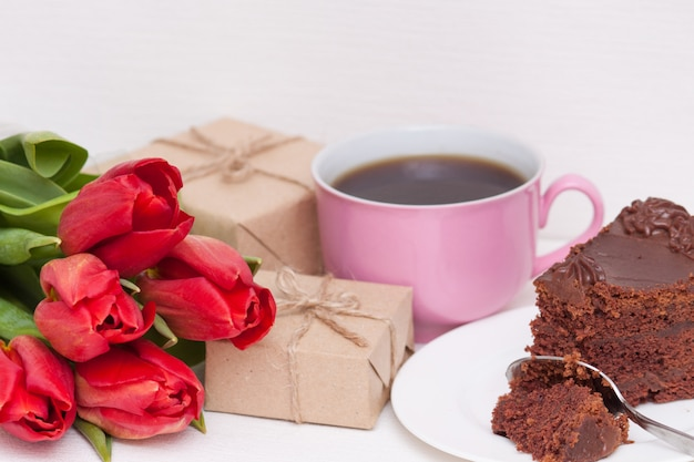 Tulipanes, regalos, pastel, taza para la madre, esposa, hija, niña con amor. feliz cumpleaños,