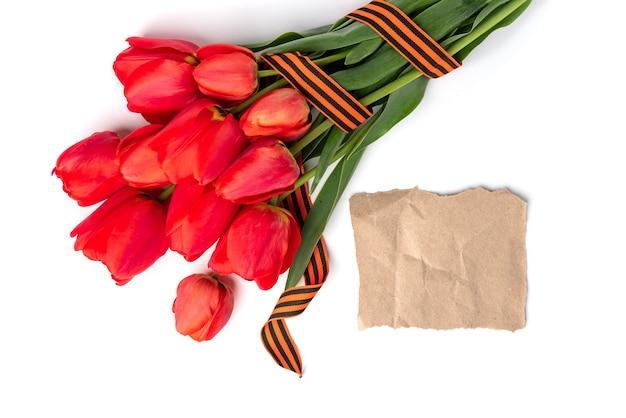 Tulipanes rojos con cinta de san jorge sobre fondo blanco. día de la victoria o día del defensor de la patria.