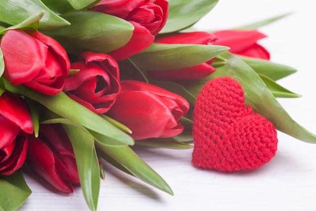 Tulipanes rojos delicados en un fondo de madera blanco. de cerca. composición de las flores. fondo floral de la primavera. día de san valentín, semana santa, día de la madre.