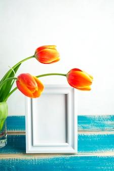 Tulipanes rojos en florero de vidrio con marco en blanco