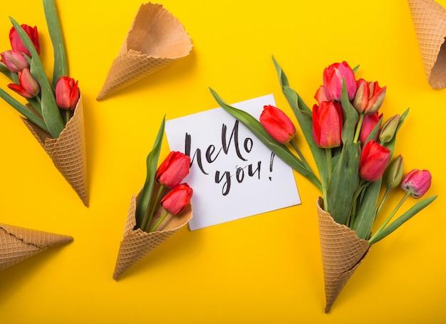 Tulipanes rojos hermosos en un cono de galleta de helado con tarjeta de tinta sobre un fondo de color amarillo. idea conceptual de un regalo de flores. humor de primavera