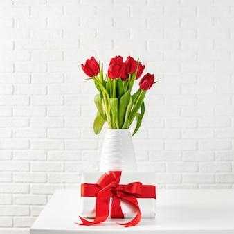 Tulipanes rojos en jarrón blanco con caja de regalo con lazo rojo