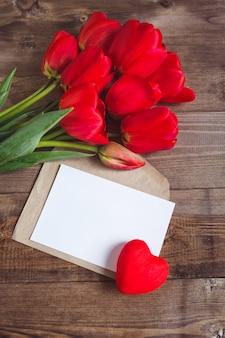 Tulipanes rojos y tarjeta de felicitación en mesa de madera, vista superior