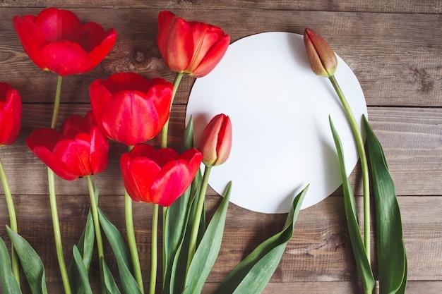 Tulipanes rojos y tarjeta de felicitación redondeada en mesa de madera, vista superior