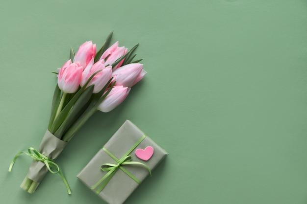 Tulipanes rosa, jacinto, cajas de regalo envueltas y corazones decorativos.