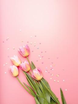 Tulipanes rosados y amarillos decorados con pequeñas formas de corazón sobre fondo rosa, vista superior plana con espacio de copia
