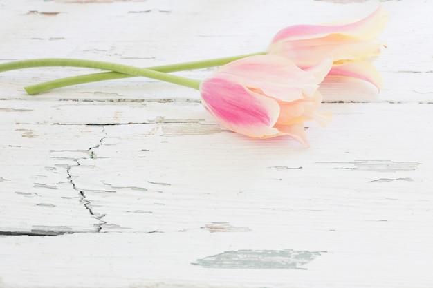 Tulipanes rosados y amarillos sobre mesa de madera pintada