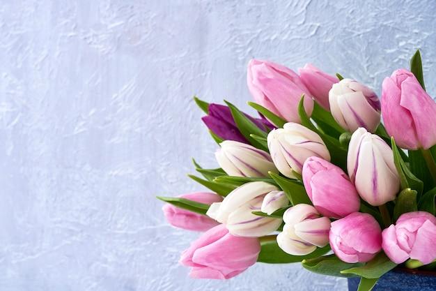 Tulipanes rosados y blancos en florero.