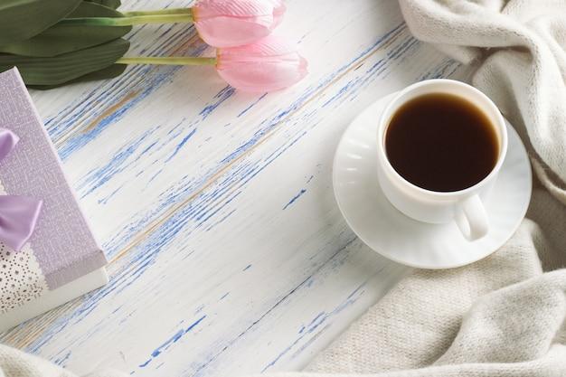 Tulipanes rosados, bufanda blanca, taza de café y caja de regalo sobre una superficie de madera blanca