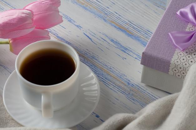 Tulipanes rosados, bufanda, taza de café y caja de regalo sobre una superficie de madera blanca
