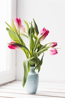 Tulipanes rosados en un florero azul junto a la ventana brillante