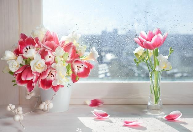 Tulipanes rosados y flores blancas de fresia en el tablero de la ventana