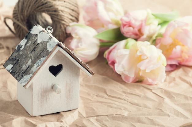 Tulipanes rosados frescos, cordel y casa para pájaros