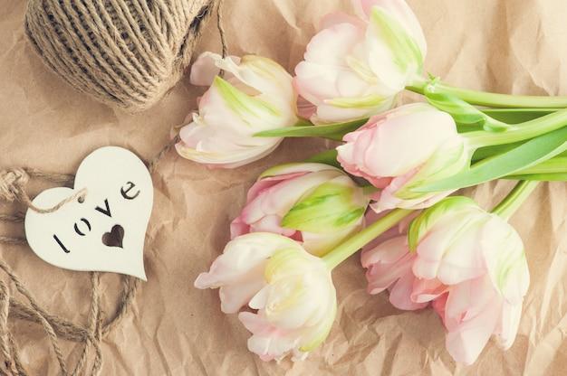Tulipanes rosados frescos, hilo y corazón