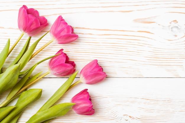 Tulipanes rosados frescos en una madera blanca, vista superior