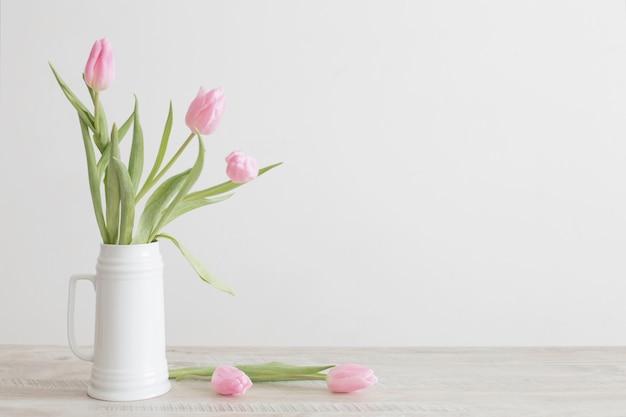 Tulipanes rosados en jarra de cerámica blanca sobre mesa de madera en la pared blanca de fondo
