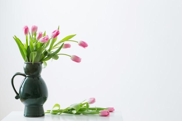 Tulipanes rosados en jarra verde sobre fondo blanco.