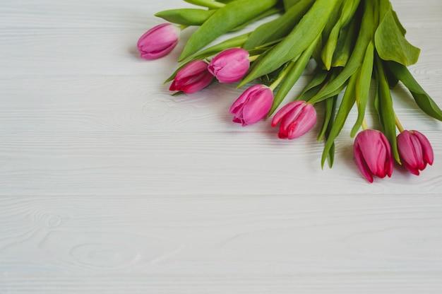 Tulipanes rosados en una mesa de madera blanca. antecedentes