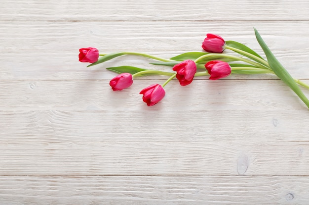 Tulipanes rosados en mesa de madera blanca