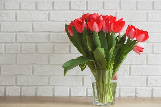 Tulipanes rosas en florero de vidrio sobre fondo de pared de ladrillo blanco.