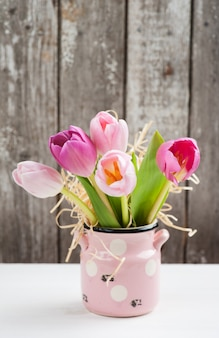 Tulipanes rosas rojas sobre fondo rústico