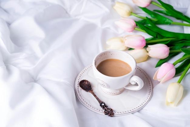 Tulipanes rosas y taza de café