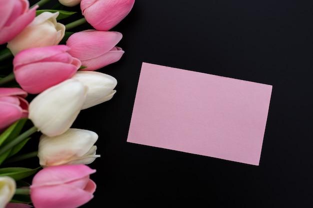 Tulipanes sobre fondo negro con tarjeta de felicitación