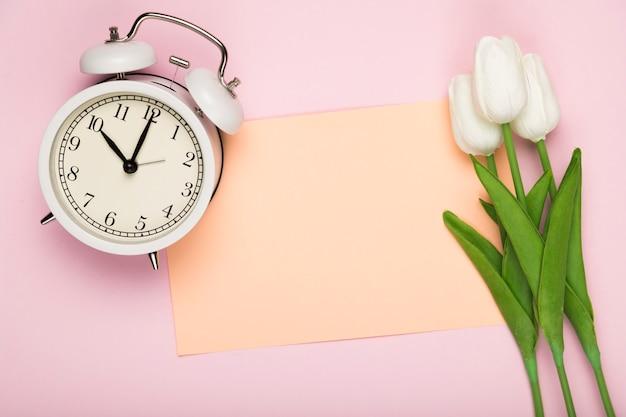 Tulipanes con tarjeta al lado del reloj